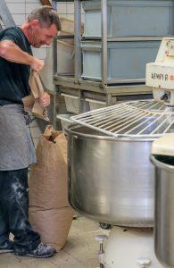 Onze bakker in de bakkerij aan het werk met de mengmachine.