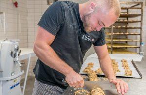 Onze broodbakker snijdt deeg in de bakkerij aan de Herenstraat in Voorburg.